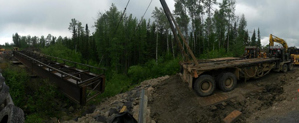 steel bridge in forest being moved by large excavator